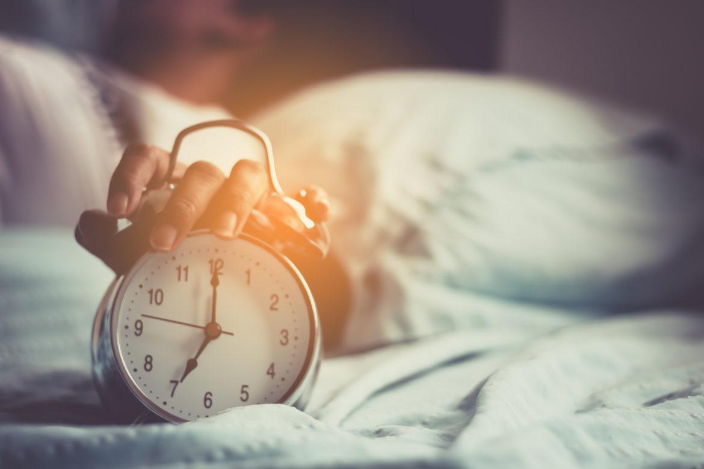 Wecker am Bett mit Hand am Morgen.