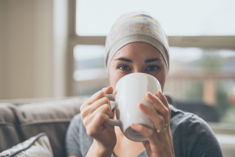 Junge Frau mit Krebs sitzt auf Couch und trinkt Tee.