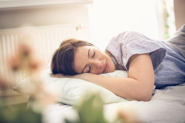 Junge Frau schläft ruhig im Bett.
