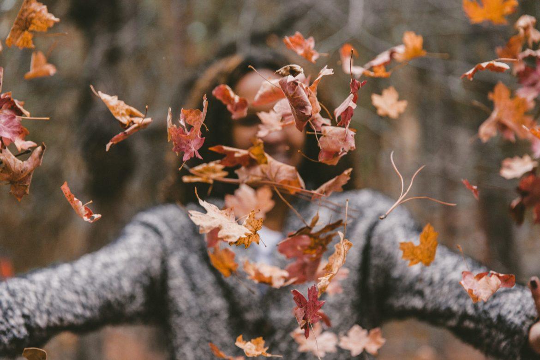 Frau wirft bunte Blätter in die Luft.