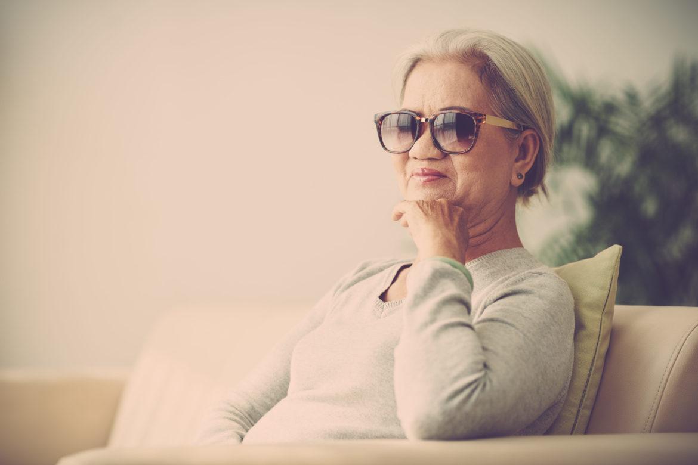 Ältere Frau mit Sonnenbrille sitzt auf dem Sofa