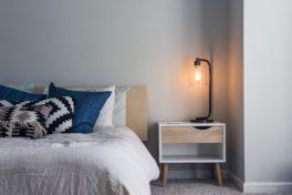 Bett mit Nachttisch, Lampe und blaue Kissen.