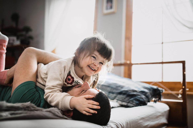 Vater und Tochter spielen und lachen auf dem Bett.