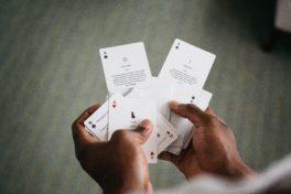 Ein Close up von von zwei Händen die Spielkarten in der Händen hält.