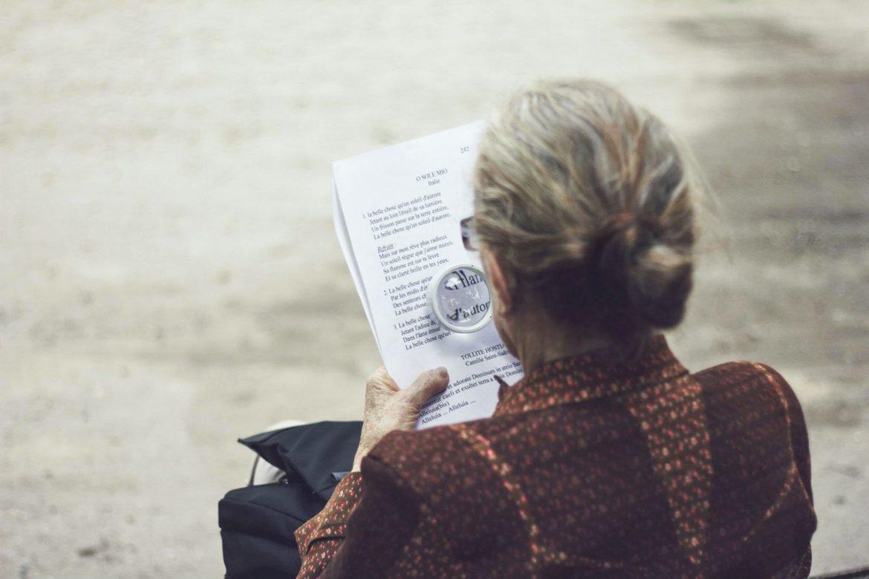 Ältere Frau liest mit einer Lupe