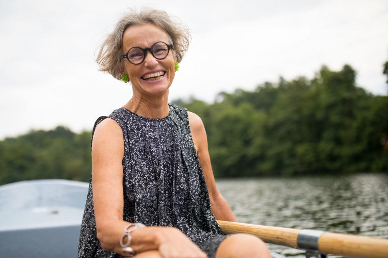 Ältere Frau mit schwarzer Brille lachend auf einem Ruderboot. - Augen