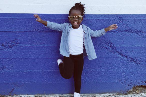 Ein dunkelhäutiges Kind steht vor einer blau-weissen Wand