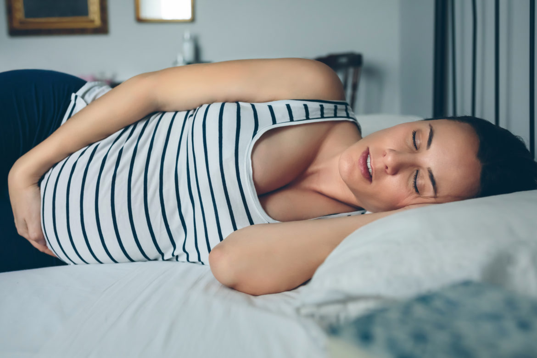 Schwangere Frau im gestreiften Tshirt schläft auf dem Bett.