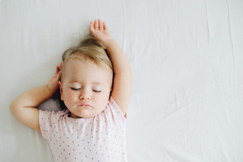 kleines Kind liegt ausgestreckt auf dem Bett uns schläft. - Schlaf