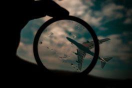 Flugzeug durch eine Linse zwischen zwei Fingern
