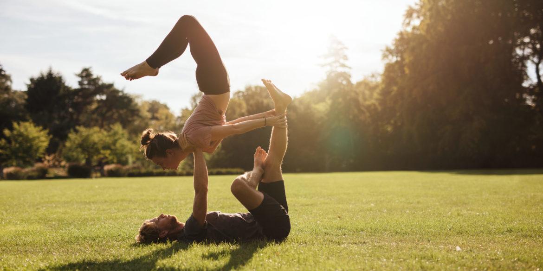 Zwei Personen machen Sportübungen auf einer grünen Wiese