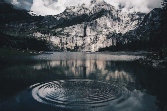 Bergsee mit leichten kreisförmigen Wellen und wolkigem Himmel.