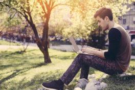 Ein junger Mann mit Laptop im Park