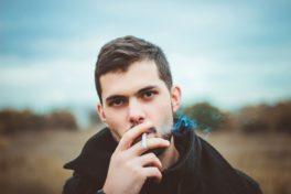 Junger Mann mit Zigarette im Mund auf einem freien Feld.