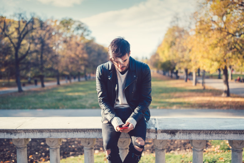 Entspannter Mann sitzt mit dem Smartphone auf einem Geländer