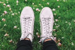 Jemand liegt mit einem Paar weisser Sneakers auf einer Wiese