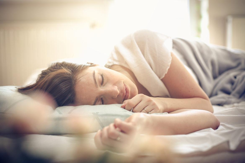 Junge Frau liegt im Bett und schläft