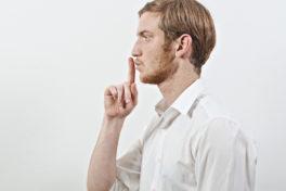 Mann hält Zeigefinger vor den Mund zum Schweigen