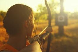 Weibliche Bogenschützin in einem Feld bei Sonnenuntergang