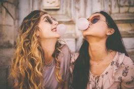 Zwei Mädchen machen Kaugummiblasen mit Kaugummi