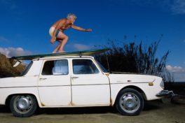 Älterer Mann surft auf einem weissen Auto