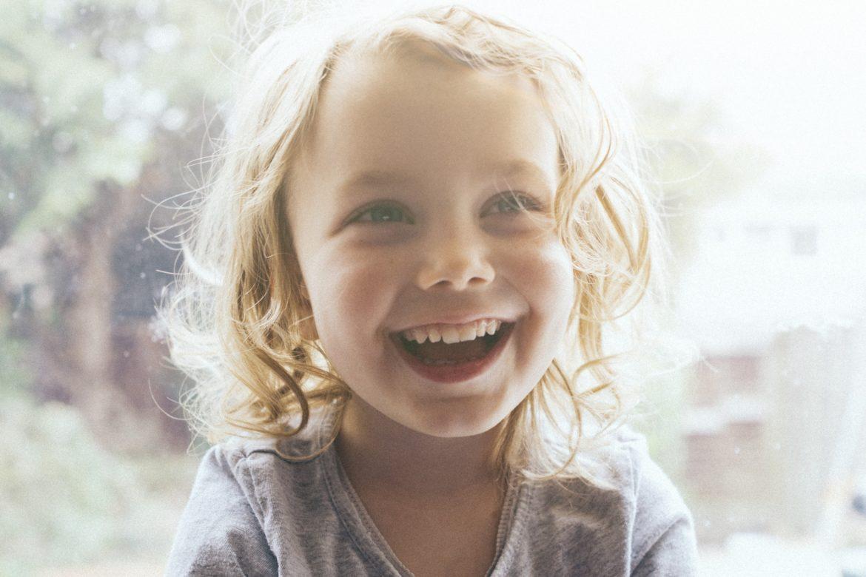 Lächelndes Kind mit Sonnenstrahlen im Gesicht