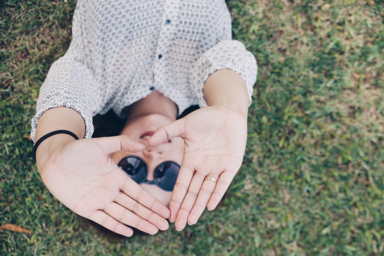 Frau auf Wiese mit Sonnenbrille macht Herz mit Hand. - Herzinfarkt