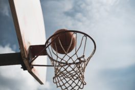 Basketball der in ein Basketballnetz fällt.