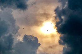 Himmel mit dunklen Wolken und Sonne.