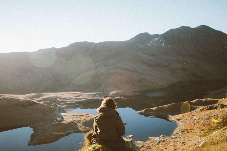 Eine Frau sitzt auf einem Felsen und schaut auf einen Fluss, der sich zwischen den Bergen durchschlängelt und Adventskalendertürchen 10.