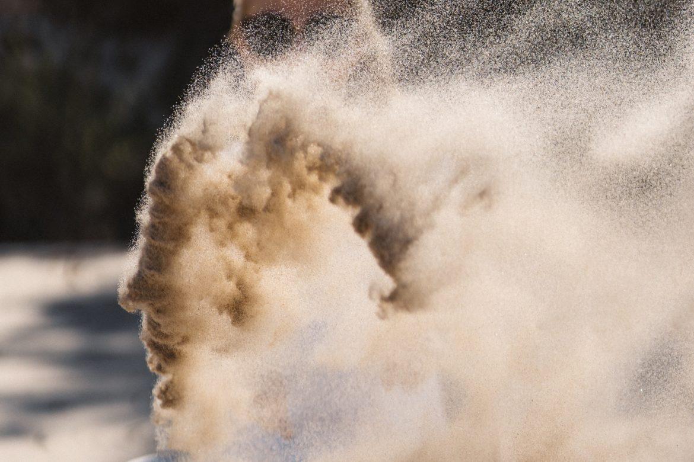 Eine Frau wirft Sand in die Sonne.