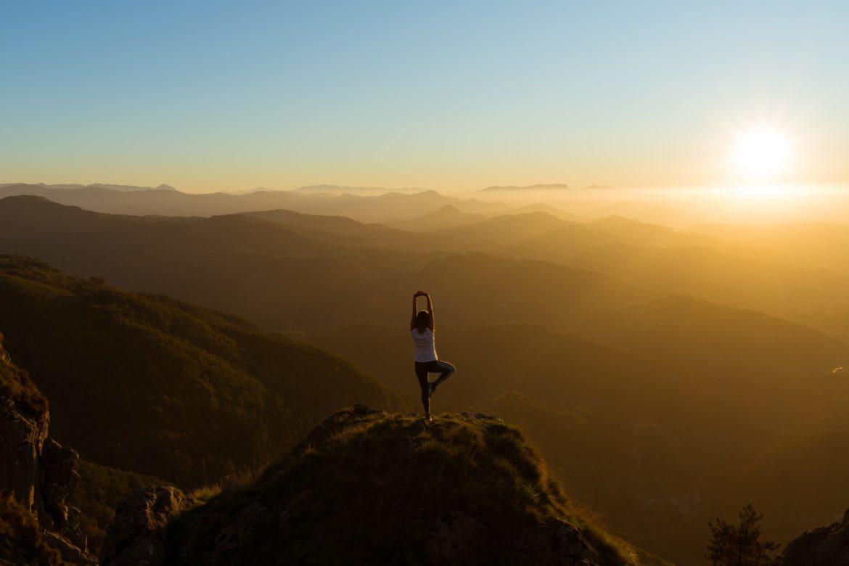 Frau macht Yoga auf einem berg bei Sonnenaufgang. _Psyche und Krebs
