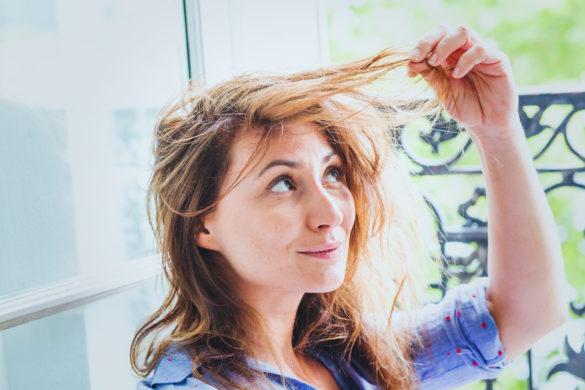 Frau hält Haare und sieht nachdenklich aus