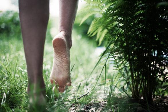 Junge Frau läuft barfuss über Gras.