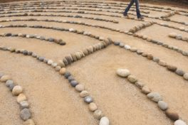 Labyrinth mit Steinen auf Sand - Eierstockkrebs Achtung Alarmsignale
