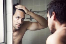 Mann schaut seine Haare an im Spiegel
