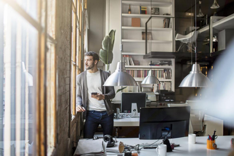 Ein Mann steht in seinem Büro mit dem Handy in der Hand