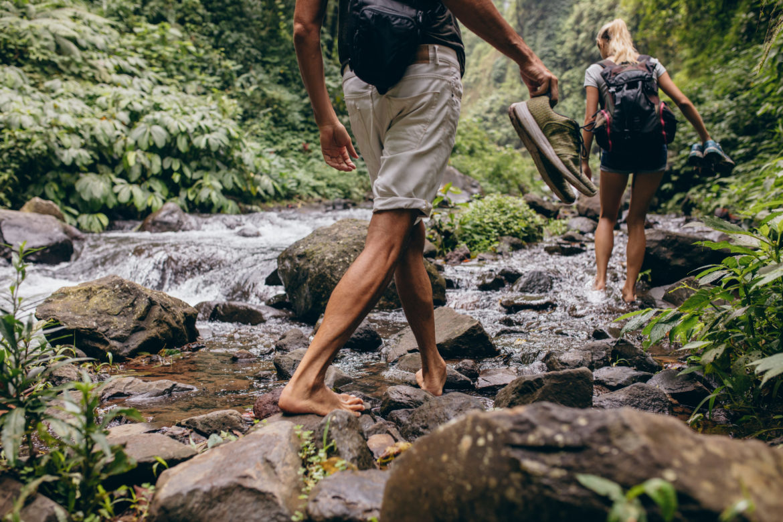 Ein Paar läuft barfuss über einen Fluss