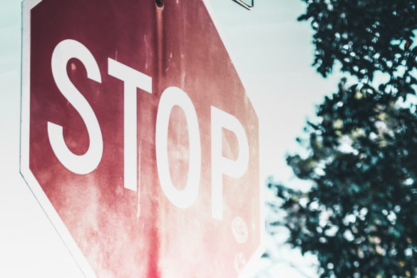 Ein Stop Schild auf einer Strasse mit Bäumen