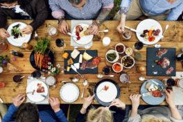 Eine Gruppe von Menschen, die zusammen an einem Holztisch isst