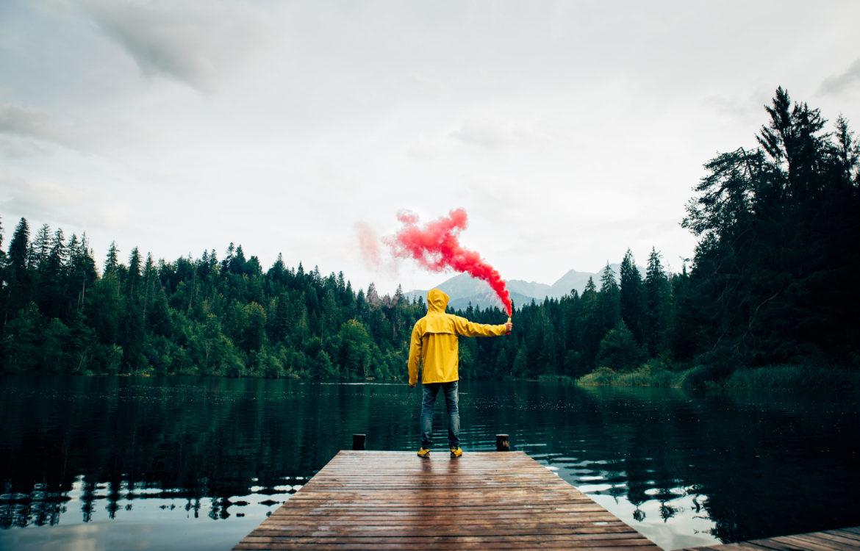 Ein Mann steht auf dem Steg an einem See mit einer Rauchfackel