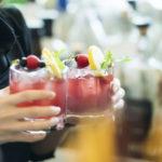 Ein Barkeeper hält zwei alkoholische Getränke.