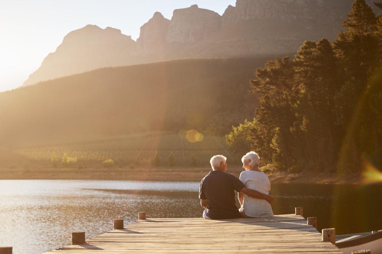 Ein älteres Paar sitzt gemeinsam auf dem Steg am See