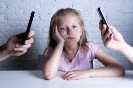 Ein Mädchen stützt genervt ihren Kopf auf zwischen zwei Handys