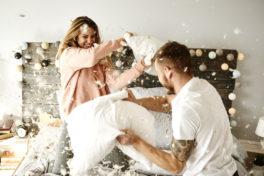 Ein Paar hat Spass bei einer Kissenschlacht