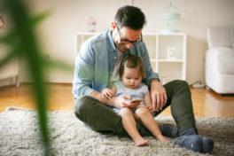 Ein Vater sitzt mit seiner Tochter auf dem Schoss auf dem Fussboden und hat ein Smartphone in der Hand