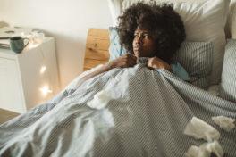 Eine junge Frau liegt krank im Bett