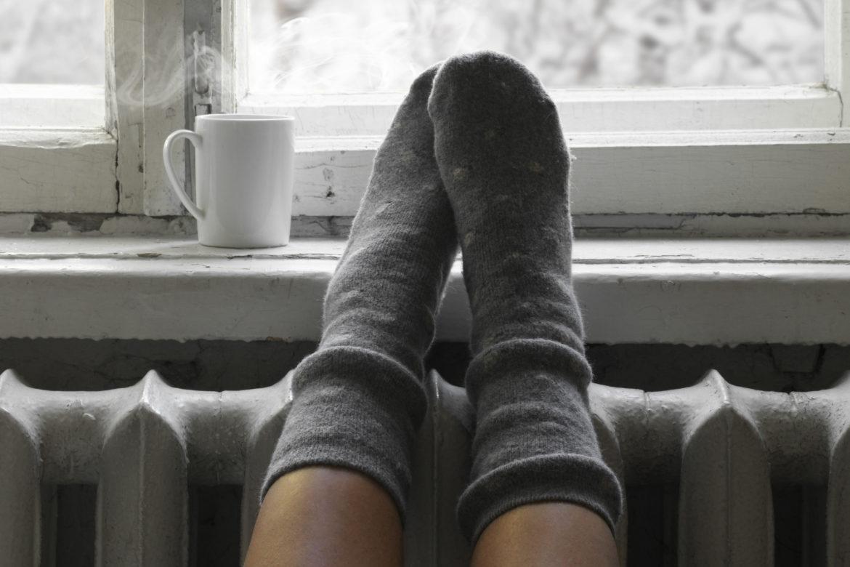 Füsse in warmen Socken liegen auf einer Heizung vor einem Fenster mit heissem Tee auf dem Fensterbrett.