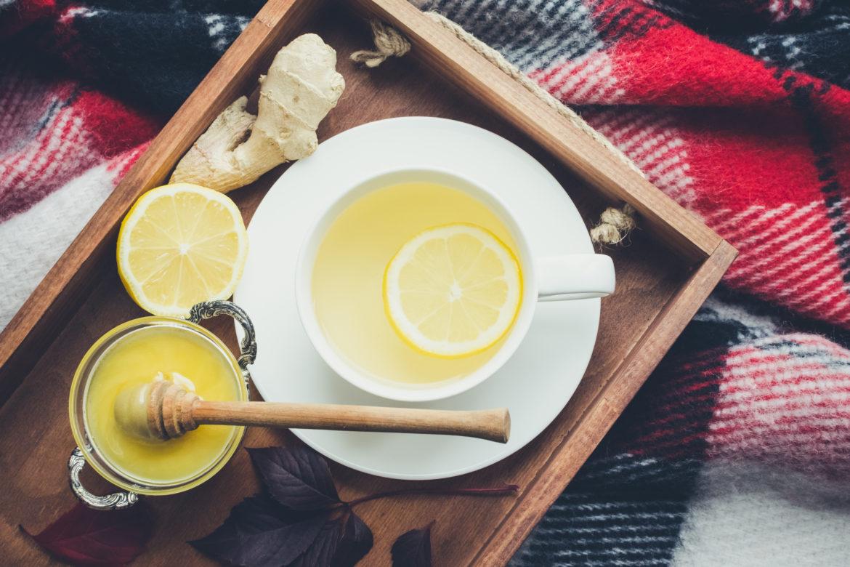Ein Tablett mit Zitrone, Honig und einer Tasse Tee auf einem Küchentuch