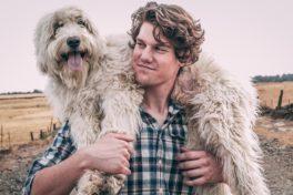 Mann trägt einen Hund über den Schultern